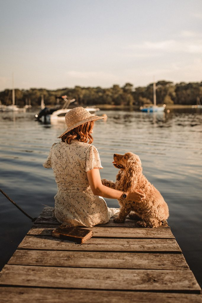Femme et son chien sur un ponton au bord du lac