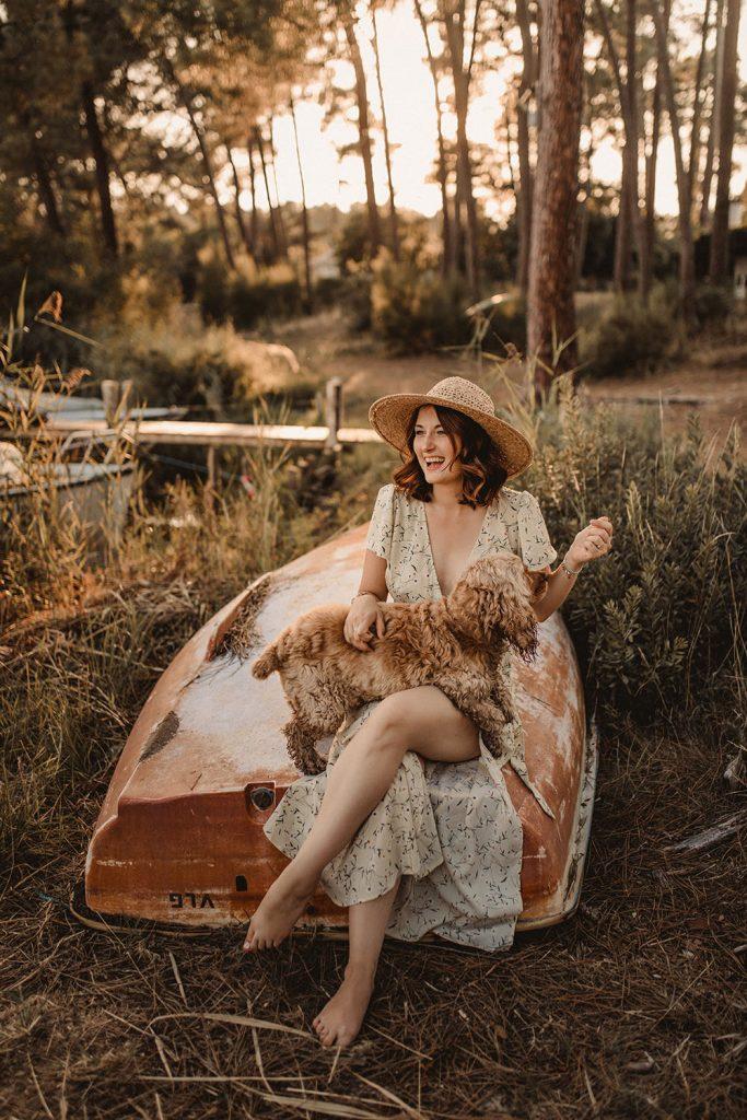 femme assise dans une foret de pin au soleil couchant en train de jouer avec son chien