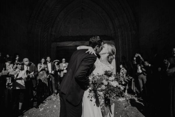 couple qui s'embrasse a la sortie de l'église sous les applaudissements de leurs invités