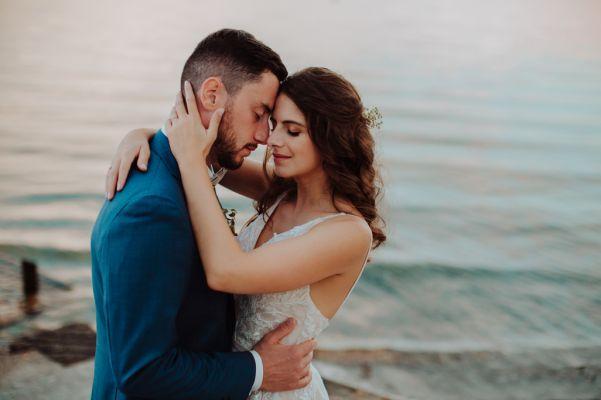 photo d'un couple de mariés devant un lac au coucher du soleil