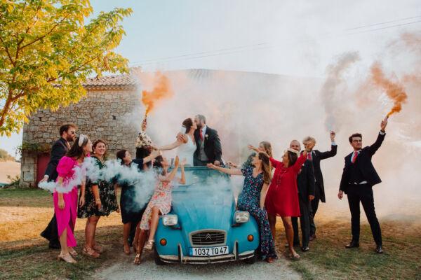 mariés dans une voiture vintage pendant que les invités sont autour avec des fumigènes