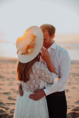 Couple s'embrassant avec un chapeau fleuri