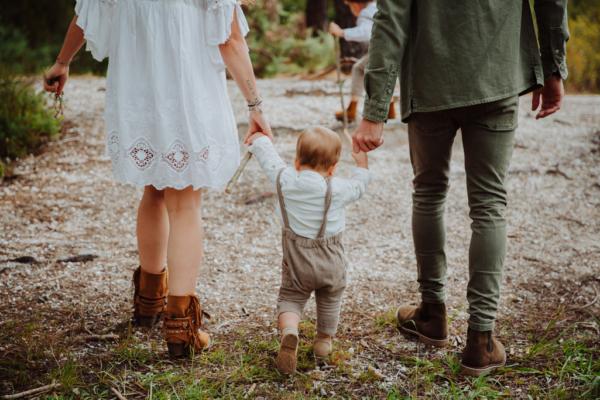 bebe de dos qui marche avec papa et maman qui lui tiennent la main